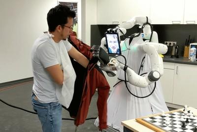 hilft einer assistenzbedürftigen Person in die Jacke. © Universität Bonn, Autonome Intelligente Systeme