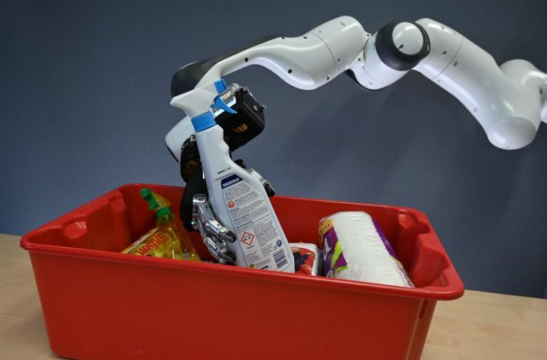 Right click to download: Roboter mit menschenähnlicher Hand beim Griff in die Kiste