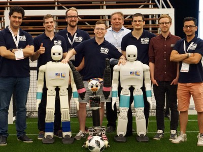 Prof. Dr. Sven Behnke (back row, middle) with his Team NimbRo featuring two adultsize-class robots. Photo credit: Team NimbRo/Uni Bonn